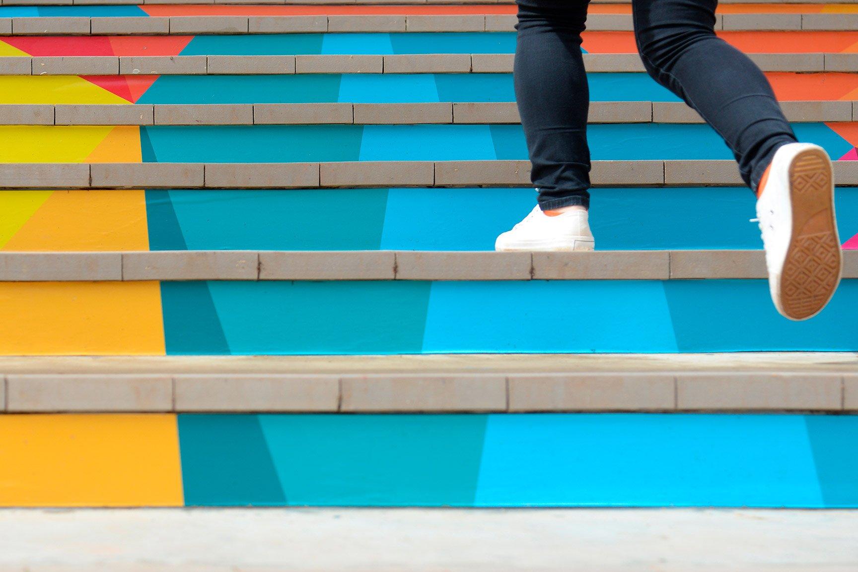 Mujer subiendo escalas de colores